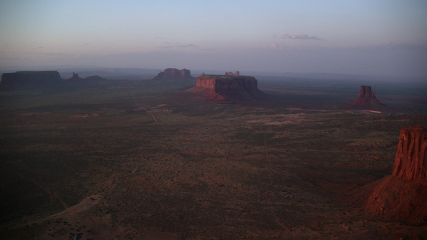 Flying by Sentinel Mesa, buttes, Monument Valley, Utah, Arizona, twilight Aerial Stock Footage | AX133_227