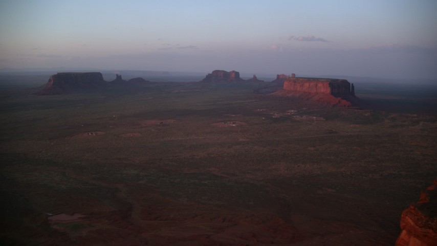 Flying by buttes and mesas, through haze, Monument Valley, Utah, Arizona, twilight Aerial Stock Footage | AX133_229