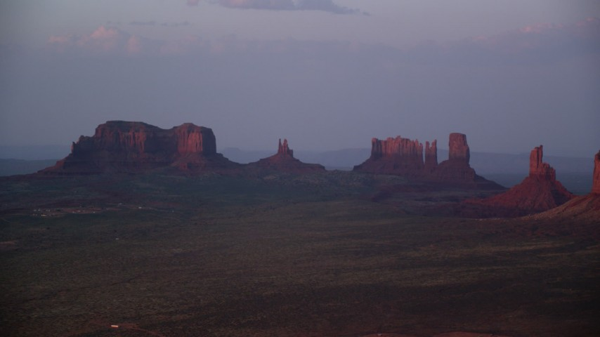 Flying by buttes in a hazy valley, Monument Valley, Utah, Arizona, twilight Aerial Stock Footage | AX133_231