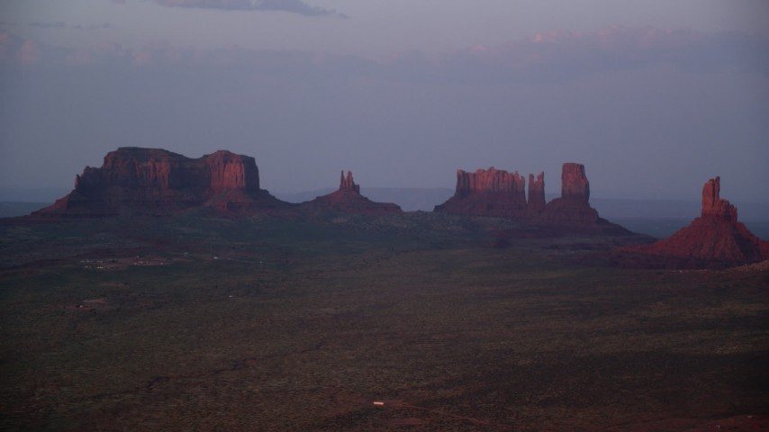 Flying by buttes, hazy desert valley, Monument Valley, Utah, Arizona, twilight Aerial Stock Footage | AX133_232