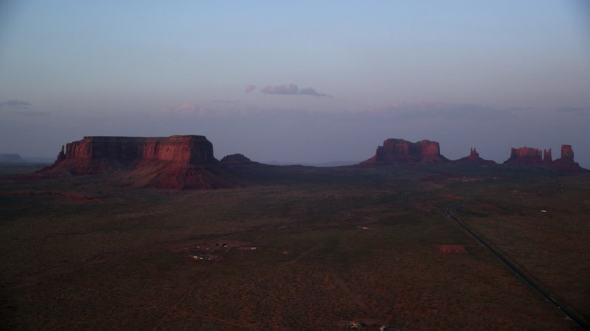 Flying by highway, mesa, buttes, Monument Valley, Utah, Arizona, twilight Aerial Stock Footage | AX133_233