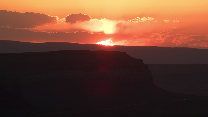 Flying by setting sun beyond a mesa, Monument Valley, Utah, Arizona, sunset Aerial Stock Footage | AX134_002