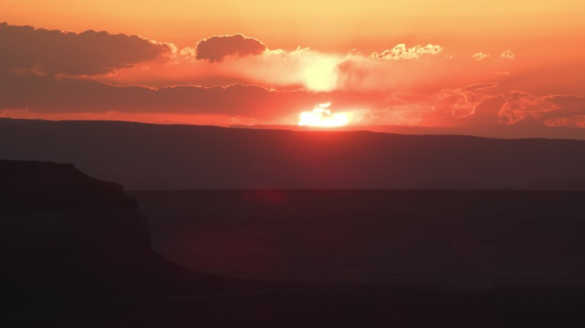 6K stock footage aerial video of flying by setting sun, seen from a mesa, Monument Valley, Utah, Arizona, sunset Aerial Stock Footage | AX134_003