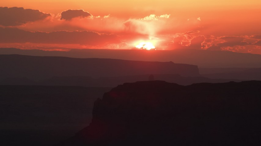 Flying by setting sun beyond mesas, Monument Valley, Utah, Arizona, sunset Aerial Stock Footage | AX134_006