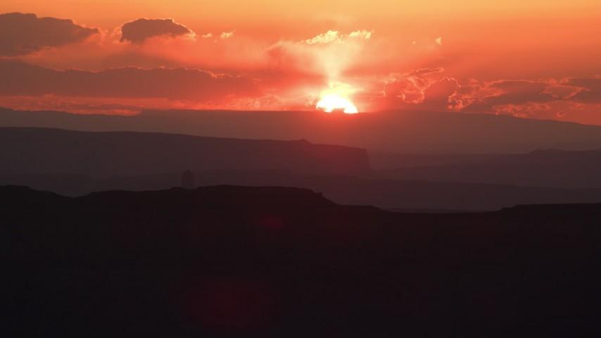 6K stock footage aerial video of flying by sun setting behind mesas in Monument Valley, Utah, Arizona, sunset Aerial Stock Footage | AX134_007