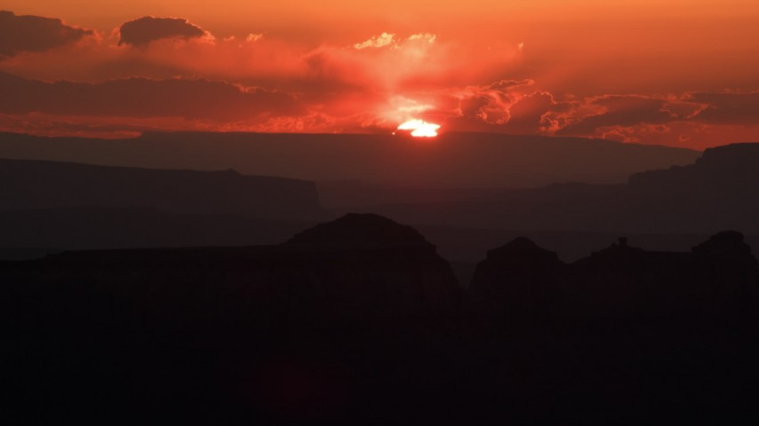 Flying by setting sun behind mesas, Monument Valley, Utah, Arizona, sunset Aerial Stock Footage | AX134_008