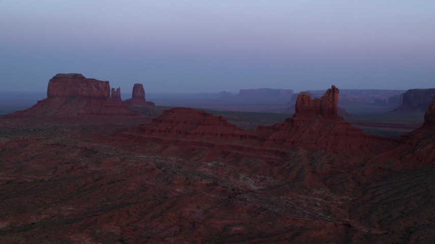 Flying by Setting Hen Butte, Monument Valley, Utah, Arizona, twilight Aerial Stock Footage | AX134_011
