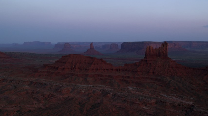 Flying by Setting Hen Butte, Monument Valley, Utah, Arizona, twilight Aerial Stock Footage | AX134_012