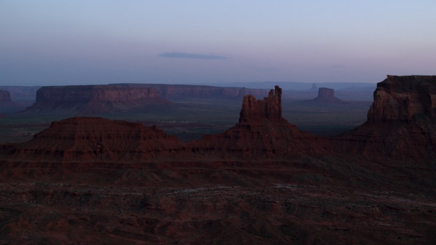 Flying by Setting Hen Butte, Monument Valley, Utah, Arizona, twilight Aerial Stock Footage | AX134_013