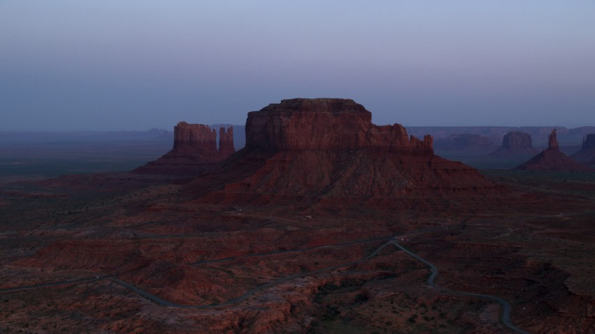 Flying by Brighams Tomb Butte, Monument Valley, Utah, Arizona, twilight Aerial Stock Footage | AX134_014