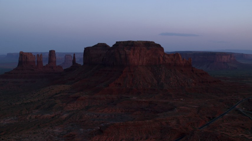 6K stock footage aerial video of flying by buttes and hazy desert valley, Monument Valley, Utah, Arizona, twilight Aerial Stock Footage | AX134_015