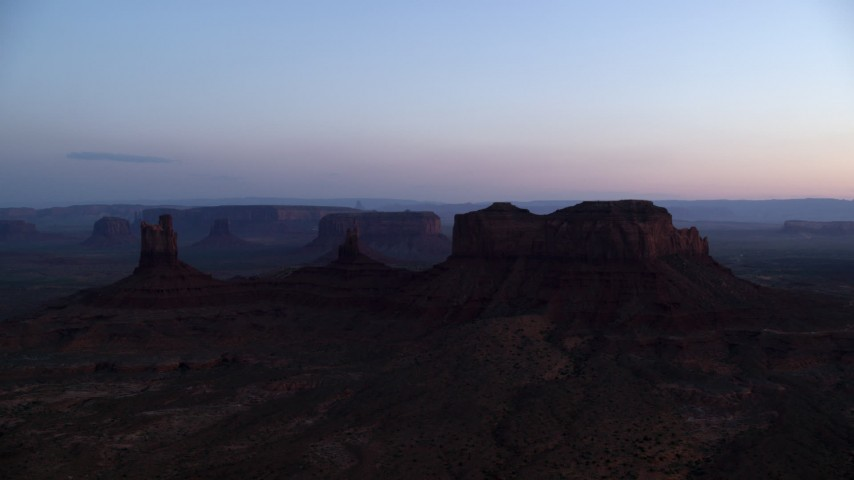 Flying by buttes, seen through haze, Monument Valley, Utah, Arizona, twilight Aerial Stock Footage | AX134_018