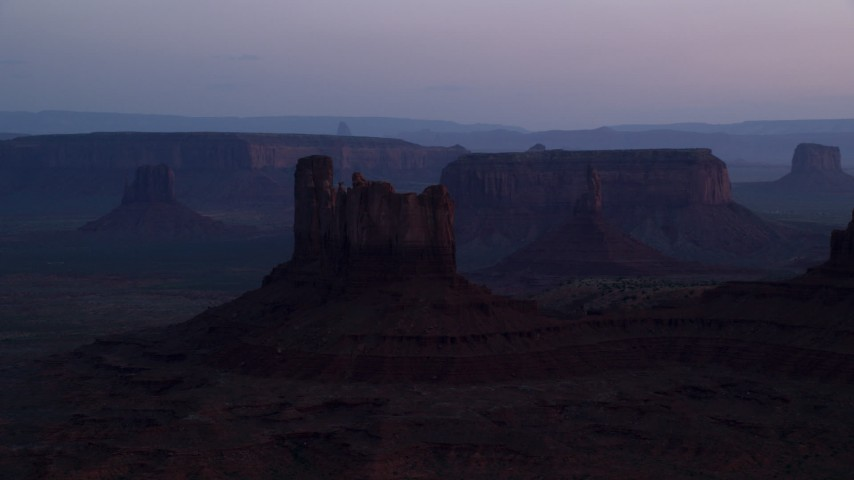 Flying by buttes, mesas through haze, Monument Valley, Utah, Arizona, twilight Aerial Stock Footage | AX134_019