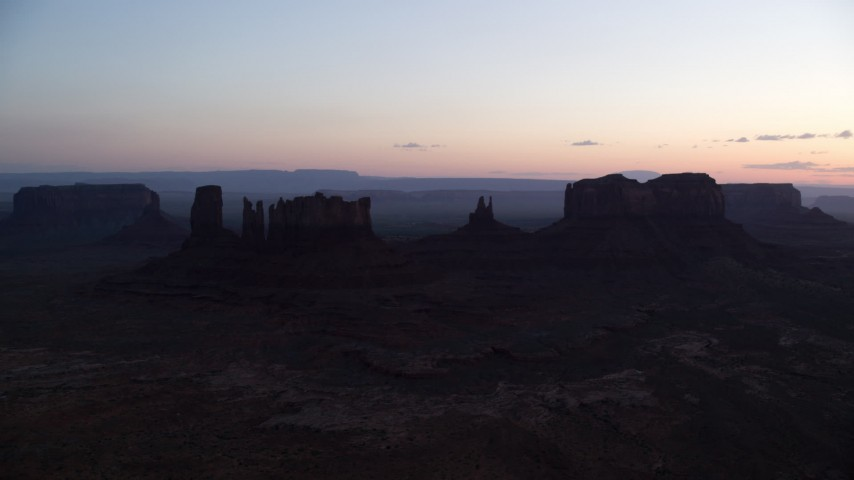 Flying by buttes through haze, Monument Valley, Utah, Arizona, twilight Aerial Stock Footage | AX134_021