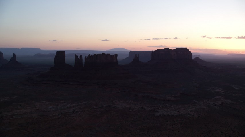 Flying by buttes through layer of haze, Monument Valley, Utah, Arizona, twilight Aerial Stock Footage | AX134_023