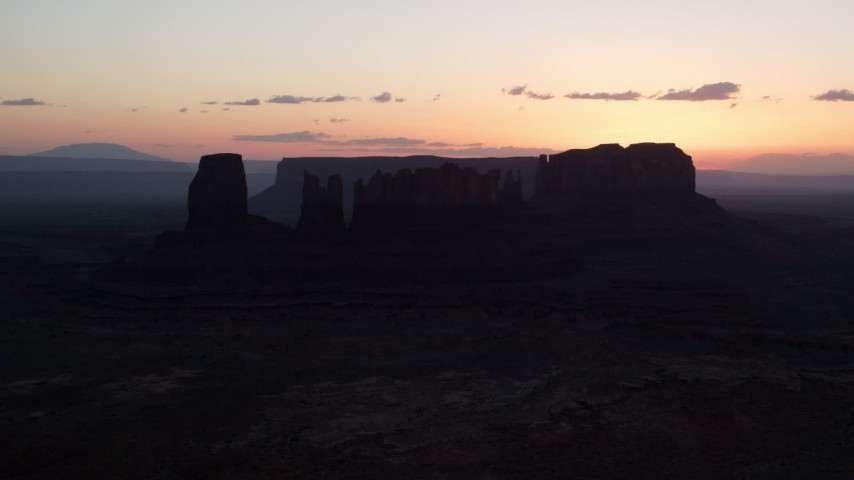 Flying by buttes, through layer of haze, Monument Valley, Utah, Arizona, twilight Aerial Stock Footage | AX134_024