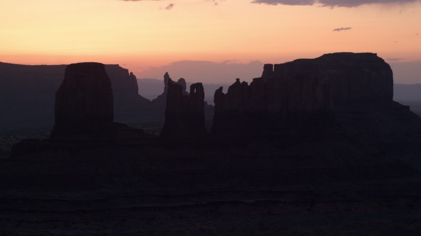 Flying by buttes, through layer of haze, Monument Valley, Utah, Arizona, twilight Aerial Stock Footage | AX134_025