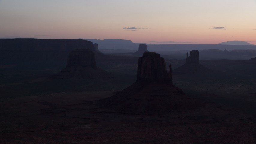 Flying by buttes, Monument Valley, Utah, Arizona, twilight Aerial Stock Footage | AX134_029