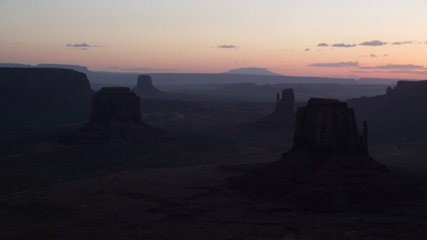 Flying by buttes, Monument Valley, Utah, Arizona, twilight Aerial Stock Footage | AX134_030