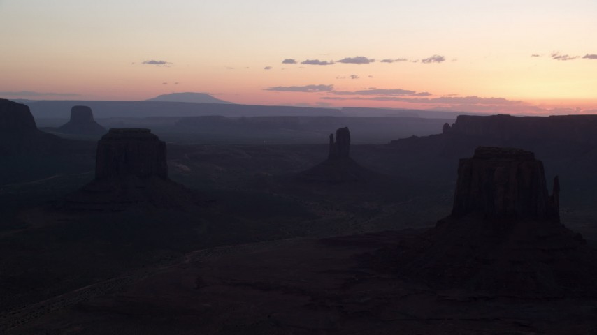 Flying by buttes, Monument Valley, Utah, Arizona, twilight Aerial Stock Footage | AX134_031