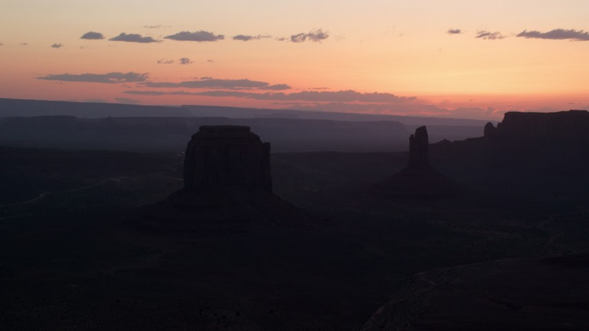Flying by Merrick Butte, West Mitten Butte,  Monument Valley, Utah, Arizona, twilight Aerial Stock Footage | AX134_032