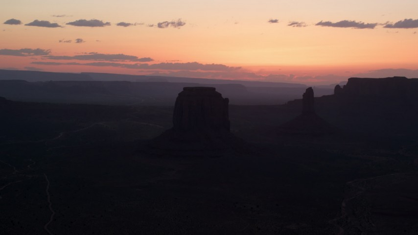 Flying by Merrick Butte, West Mitten Butte, Monument Valley, Utah, Arizona, sunset Aerial Stock Footage | AX134_033