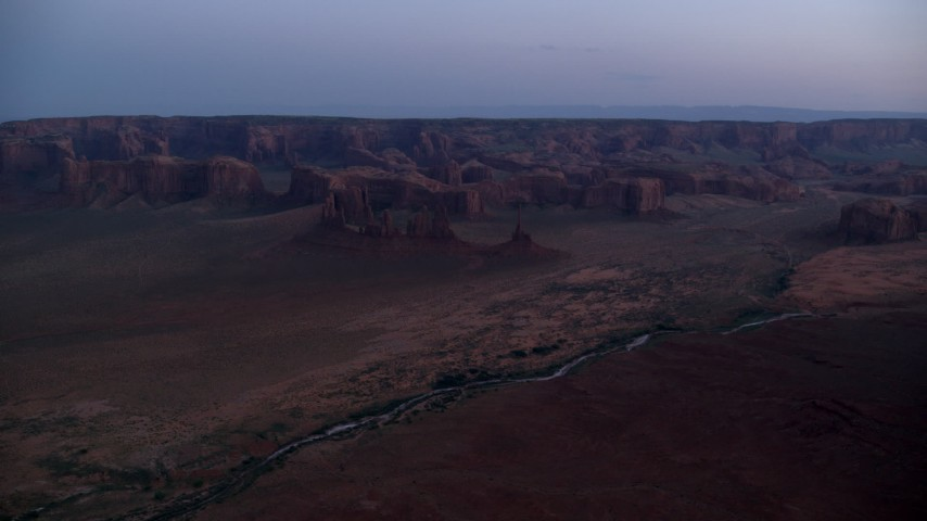 Approaching buttes and rock formations, Monument Valley, Utah, Arizona, twilight Aerial Stock Footage | AX134_034
