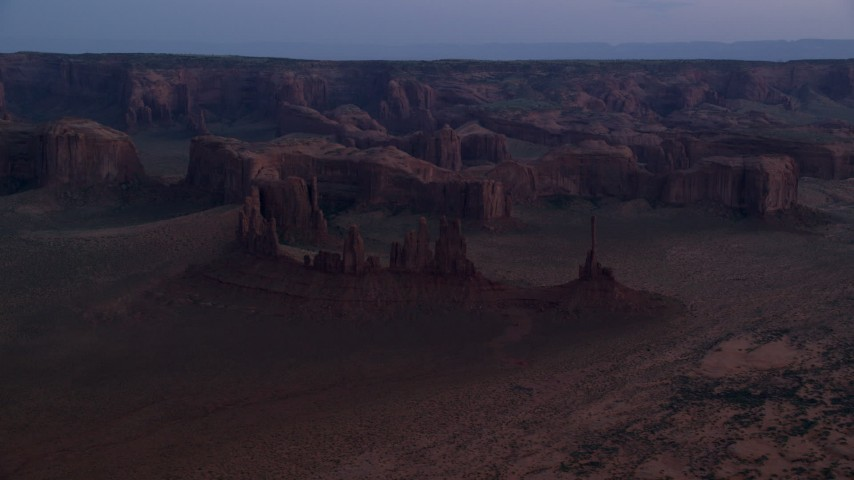 Approaching buttes and rock formations, Monument Valley, Utah, Arizona, twilight Aerial Stock Footage | AX134_036