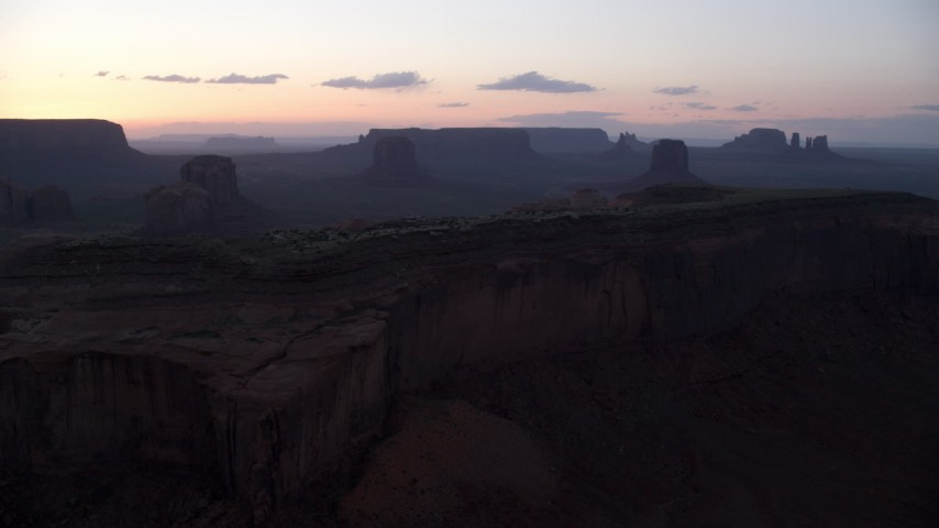 Flying by desert buttes, mesas, Monument Valley, Utah, Arizona, twilight Aerial Stock Footage | AX134_037
