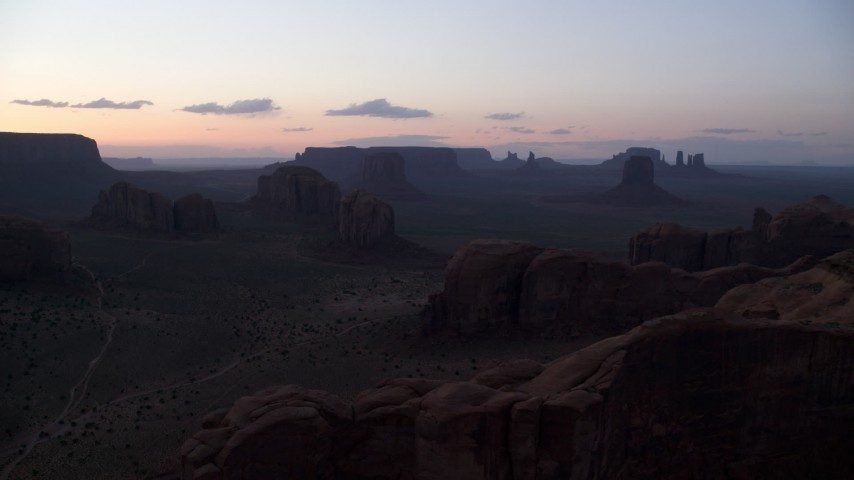 Flying by desert buttes and mesas, Monument Valley, Utah, Arizona, twilight Aerial Stock Footage | AX134_039