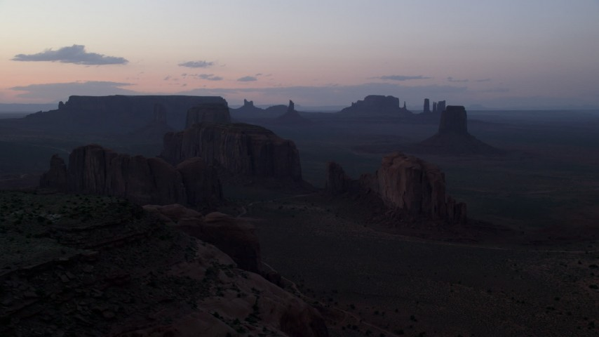 Flying by desert buttes and mesas, Monument Valley, Utah, Arizona, twilight Aerial Stock Footage AX134_041