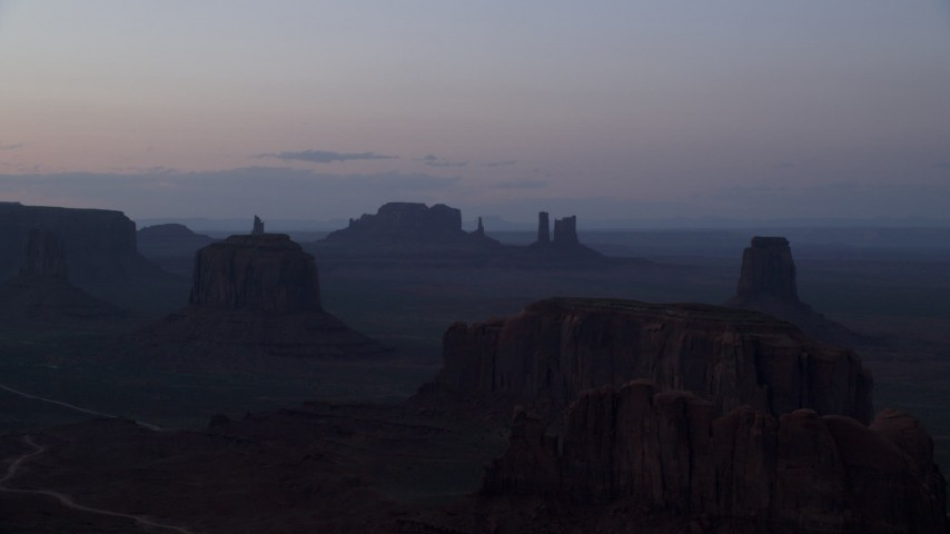 Flying by desert buttes and mesas, Monument Valley, Utah, Arizona, twilight Aerial Stock Footage | AX134_044