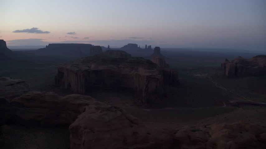 Flying by buttes and mesas, Monument Valley, Utah, Arizona, twilight Aerial Stock Footage | AX134_046