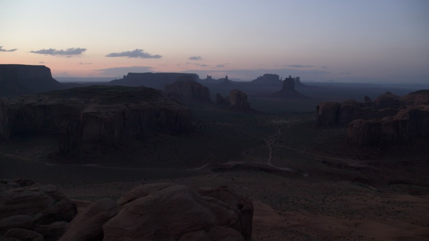 Flying by buttes and mesas, Monument Valley, Utah, Arizona, twilight Aerial Stock Footage | AX134_047