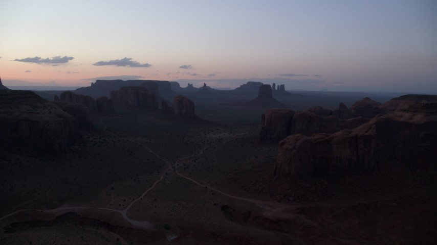 Flying by desert buttes an mesas, Monument Valley, Utah, Arizona, twilight Aerial Stock Footage | AX134_048