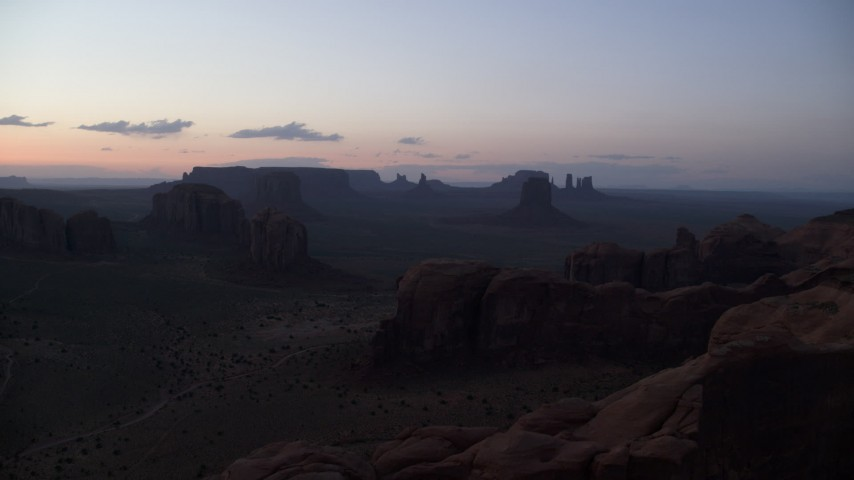 Flying by desert buttes and mesas, Monument Valley, Utah, Arizona, twilight Aerial Stock Footage | AX134_049