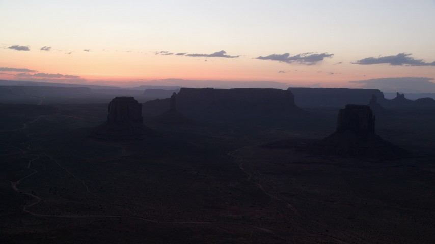 Flying by Merrick Butte, East Mitten Butte, Monument Valley, Utah, Arizona, twilight Aerial Stock Footage | AX134_053