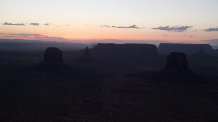 Flying by Merrick Butte, East Mitten Butte, Monument Valley, Utah, Arizona, twilight Aerial Stock Footage | AX134_054