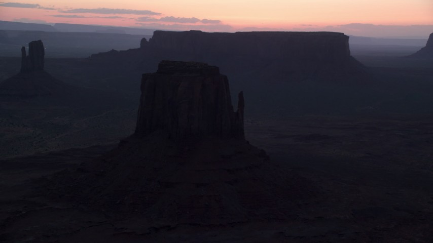 Flying by buttes, hazy desert, Monument Valley, Utah, Arizona, twilight Aerial Stock Footage | AX134_056