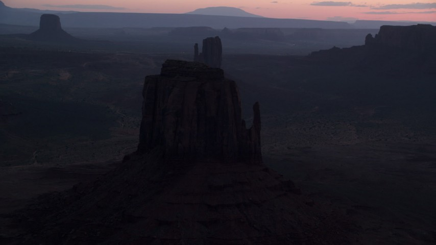 Flying by buttes, through thick haze, Monument Valley, Utah, Arizona, twilight Aerial Stock Footage | AX134_057