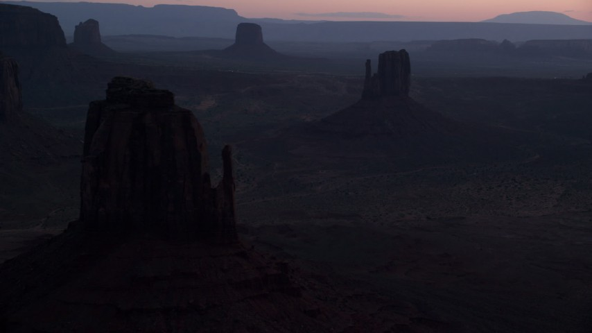 Flying by buttes through thick haze, Monument Valley, Utah, Arizona, twilight Aerial Stock Footage | AX134_058