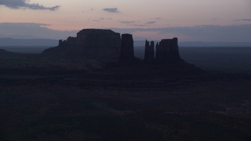 6K stock footage aerial video of flying by buttes in haze, Monument Valley, Utah, Arizona, twilight Aerial Stock Footage | AX134_059