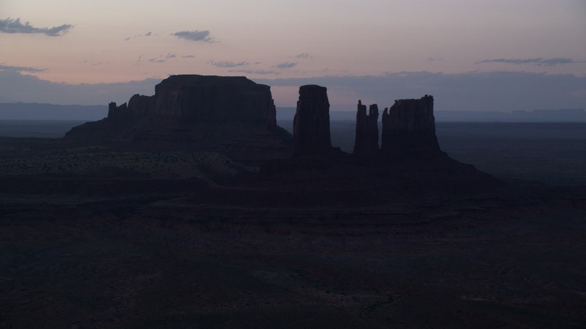 Flying by buttes through layer of haze, Monument Valley, Utah, Arizona, twilight  Aerial Stock Footage | AX134_060