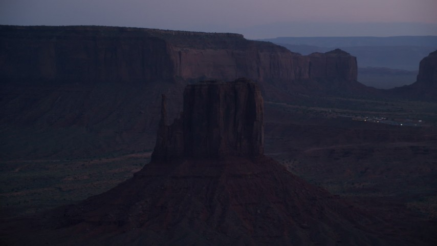 Flying by West Mitten Butte, Monument Valley, Utah, Arizona, twilight Aerial Stock Footage | AX134_061