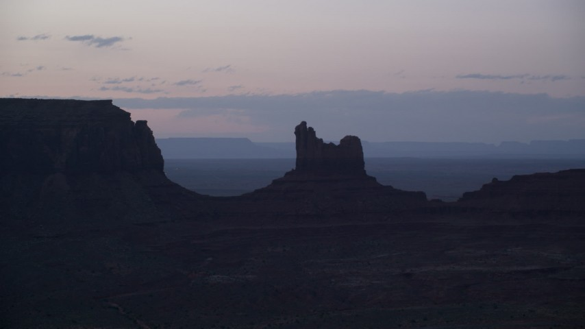 Flying by Setting Hen Butte, Monument Valley, Utah, Arizona, twilight Aerial Stock Footage | AX134_064