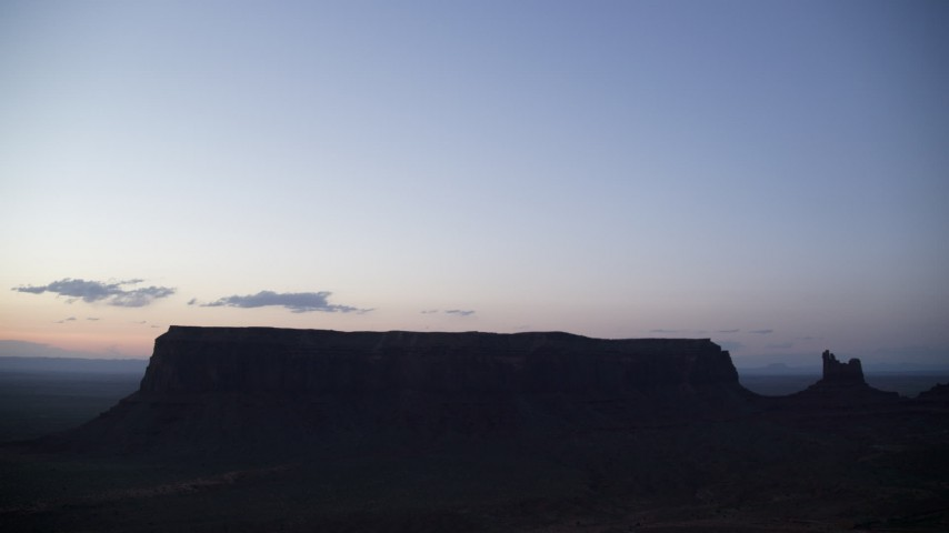 Flying by Eagle Mesa, Setting Hen Butte, Monument Valley, Utah, Arizona, twilight Aerial Stock Footage | AX134_065