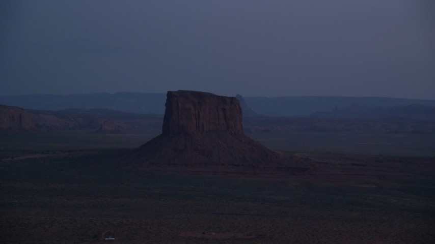 Flying by Mitchell Butte, Monument Valley, Utah, Arizona, twilight Aerial Stock Footage | AX134_067