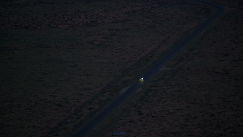 Tracking SUV on highway, desert valley, Monument Valley, Utah, Arizona, twilight Aerial Stock Footage | AX134_068