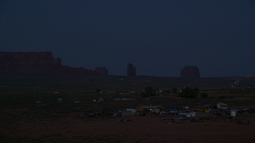 Flying by small town, buttes, Monument Valley, Utah, Arizona, night Aerial Stock Footage | AX134_075