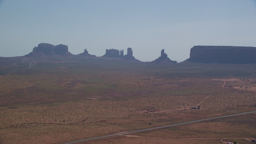 Flying by desert buttes and mesas, desert, Monument Valley, Utah, Arizona Aerial Stock Footage | AX135_004